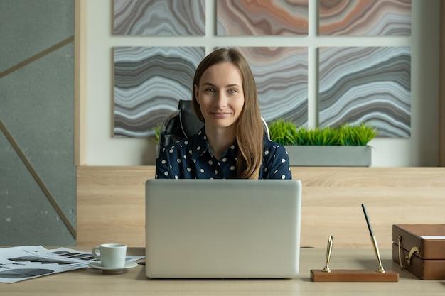 Портрет молодой женщины в рубашке, работающей на ноутбуке в офисе и смотрящей в камеру