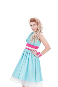 핀-업 스타일에 밝은 파란색 드레스에 젊은 여자의 초상화. 흰 벽에 절연