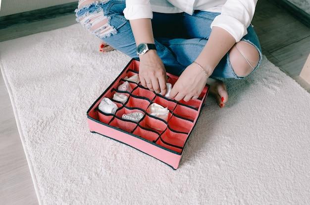 캐주얼한 옷을 입은 젊은 여성의 초상화가 용기와 상자에 물건을 아름답게 넣고 있습니다. 옷장에 액세서리와 속옷을 적절하게 보관한다는 개념