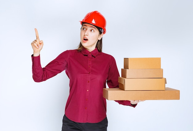 Портрет молодой женщины в защитном шлеме с бумажными коробками, указывая пальцем вверх.