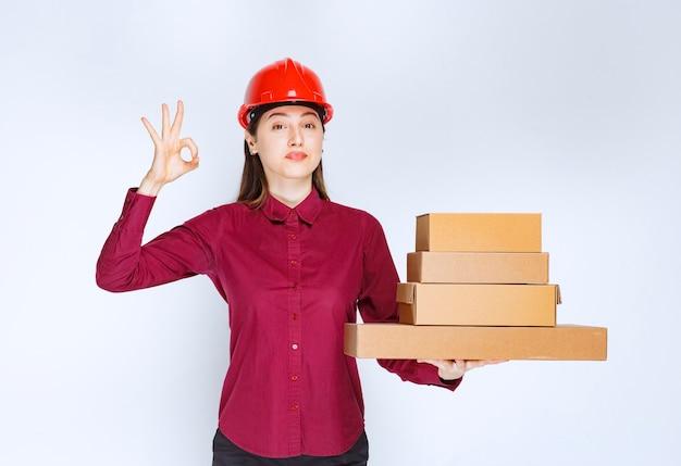 Портрет молодой женщины в защитном шлеме с бумажными коробками, показывающими одобренный жест.