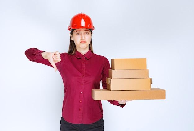 Портрет молодой женщины в защитном шлеме с бумажными коробками, показывая большой палец вниз.
