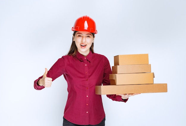 Портрет молодой женщины в защитном шлеме с бумажными коробками, показывая большой палец вверх.