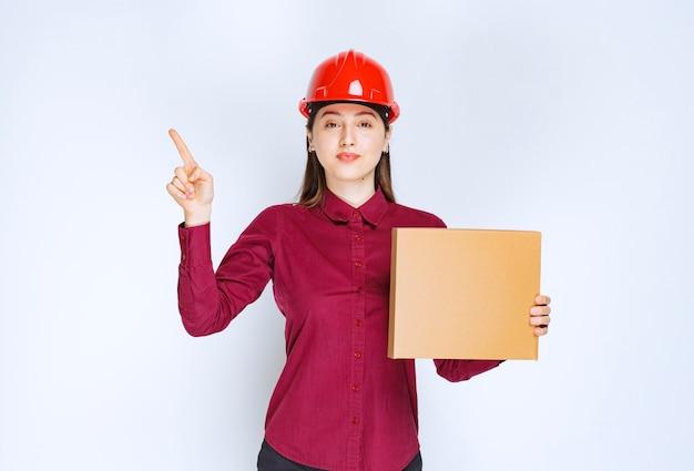 Портрет молодой женщины в защитном шлеме с небольшой бумажной коробкой, указывая пальцем вверх.
