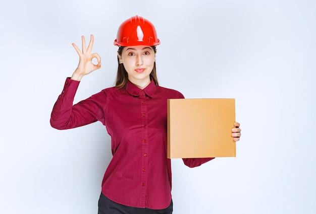 Портрет молодой женщины в защитном шлеме с небольшой бумажной коробкой, показывая одобренный жест.