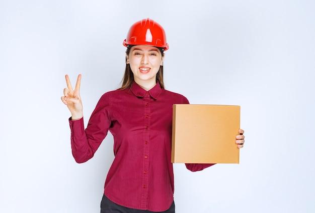 Портрет молодой женщины в защитном шлеме с небольшой бумажной коробкой, показывающей знак победы.
