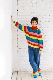 ジーンズとレインボーセーターの高品質の写真で若い女性の肖像画