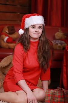 Портрет молодой женщины в шляпе помощника санта и красном платье в подготовке к рождеству дома.