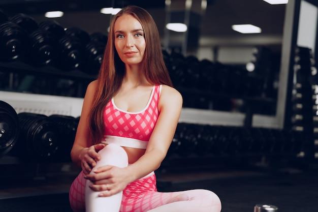 Портрет молодой женщины в спортивной одежде, позирующей в тренажерном зале