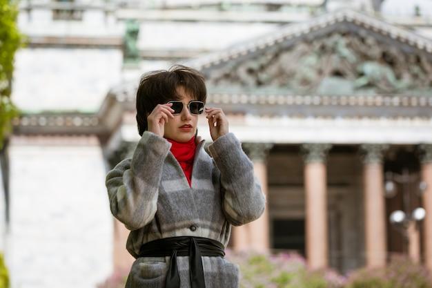 聖イサアク大聖堂を背景にコートを着たサングラスをかけた若い女性の肖像画