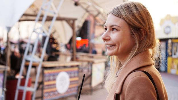 Портрет молодой женщины в городе. городской фуд-корт с уличной едой. портрет улыбающейся блондинки. фото стиля жизни
