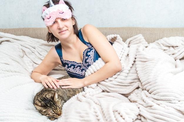 아침에 얼굴과 잠옷에 잠자는 마스크를 쓴 젊은 여성의 초상화. 근처에 회색 고양이가 자고 있습니다. 개념 아침입니다. 여자는 행복하고 웃는다