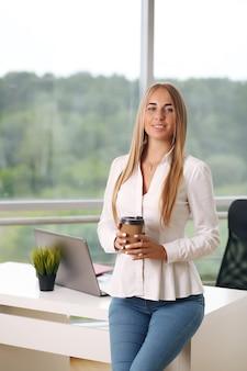 Портрет молодой женщины в офисе, держащей чашку кофе.