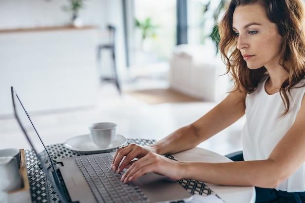 ノートパソコンを見ている若い女性の肖像画。