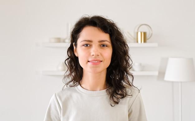 Портрет молодой женщины, глядя на камеру и улыбается. миллинале девушка с вьющимися волосами в интерьере света.