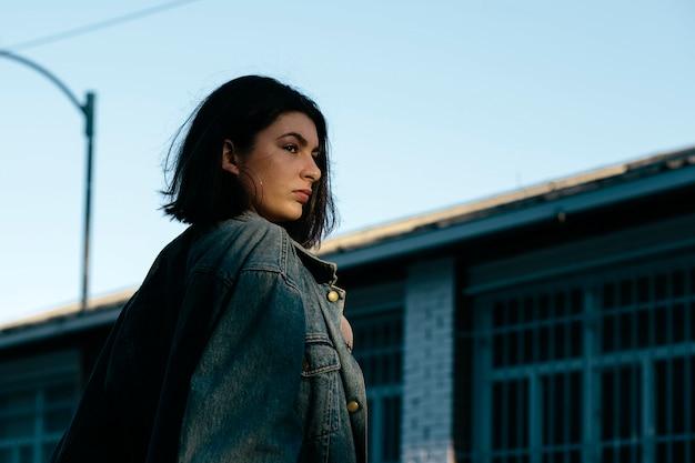 工場を背景に、通りで目をそらしている若い女性の肖像画