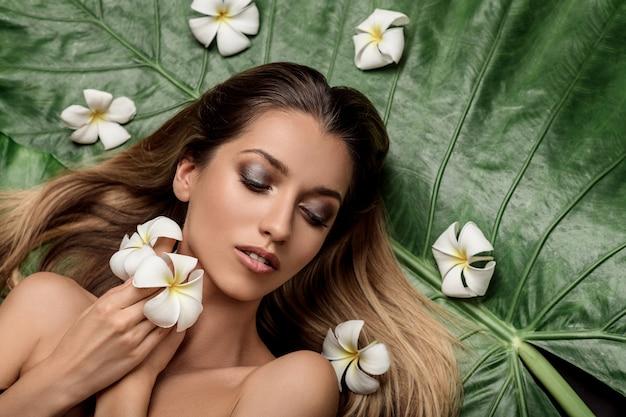 目を閉じてプルメリアの花の間に横たわっている若い女性の肖像画。美しさと若さ。スパ
