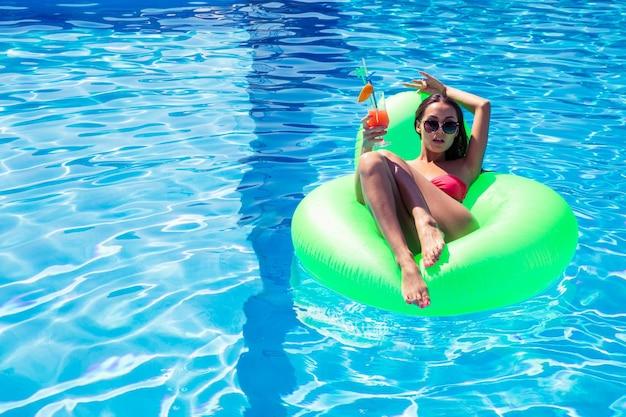Портрет молодой женщины, лежащей на надувном матрасе с коктейлем в бассейне на открытом воздухе