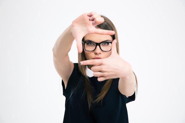 Портрет молодой женщины, делающей рамку с изолированными пальцами