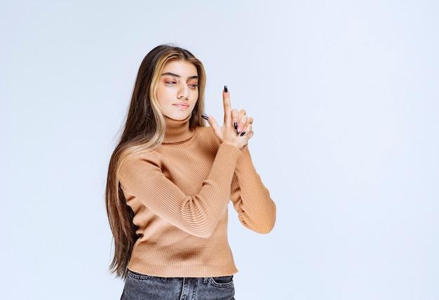 권총처럼 손가락을 들고 갈색 스웨터에 젊은 여성 모델의 초상화.