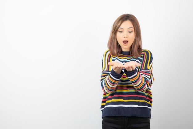開いた手のひらを示す若い女性モデルの肖像画。
