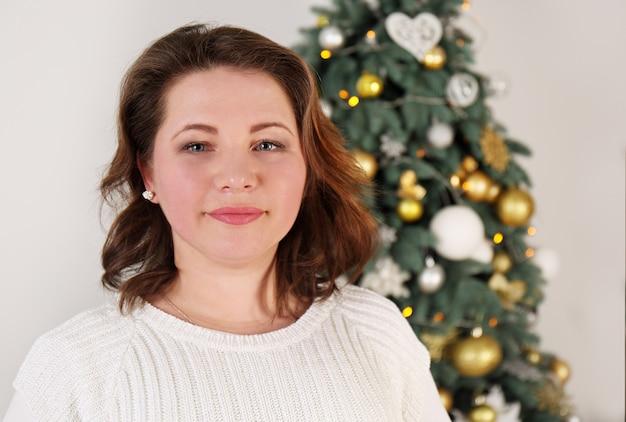 크리스마스 트리 근처 젊은 여자의 초상화