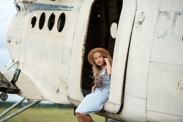 복고풍 비행기 근처 젊은 여자의 초상화. 모자와 꽃에