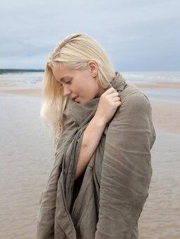자연 배경에 젊은 여자의 초상화입니다. 해변에서 아름 다운 젊은 금발 여자의 야외 초상화