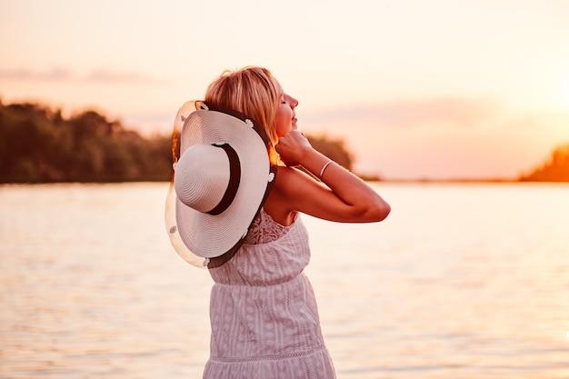 Портрет молодой женщины на фоне заката красивая счастливая блондинка в кружевном летнем д ...