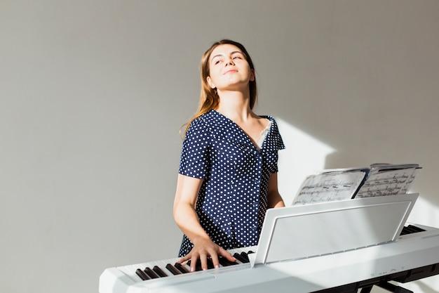 Портрет молодой женщины, играя на пианино, стоя у белой стены