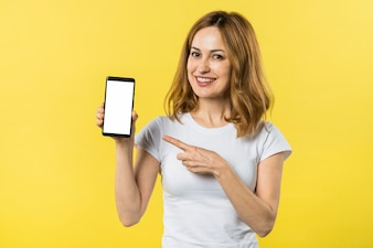 黄色の背景に対して新しいスマートフォンに向かって指を指している若い女性の肖像画