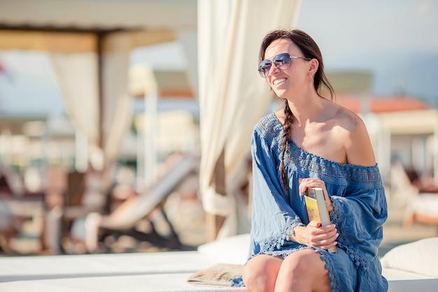 Портрет молодой женщины, отдыхая на пляже, читая книгу