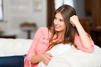 彼女の家の中のソファでリラックスしている若い女性の肖像