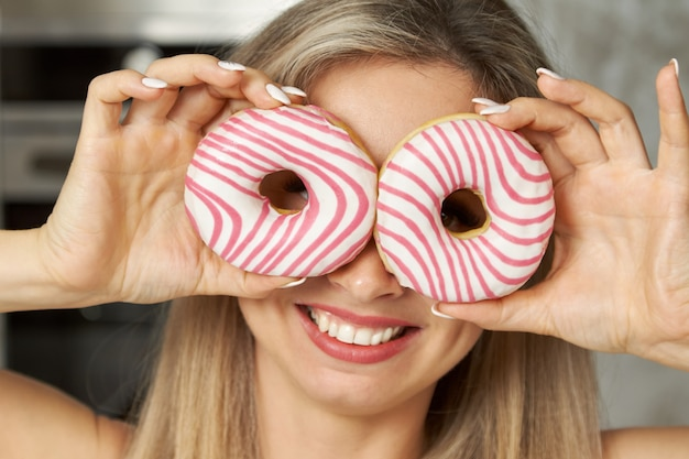 Портрет молодой женщины, улыбающейся и закрывающей глаза розово-белыми пончиками на кухне