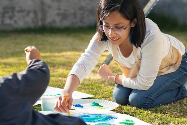 화창한 날 안뜰에서 가운을 입고 흰색 표면에 붓으로 웃고 그림을 그리는 젊은 여성의 초상화