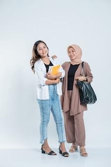 Портрет улыбающейся молодой женщины, встречающей друга по учебе, несущего сумку и книгу на изолированном белом