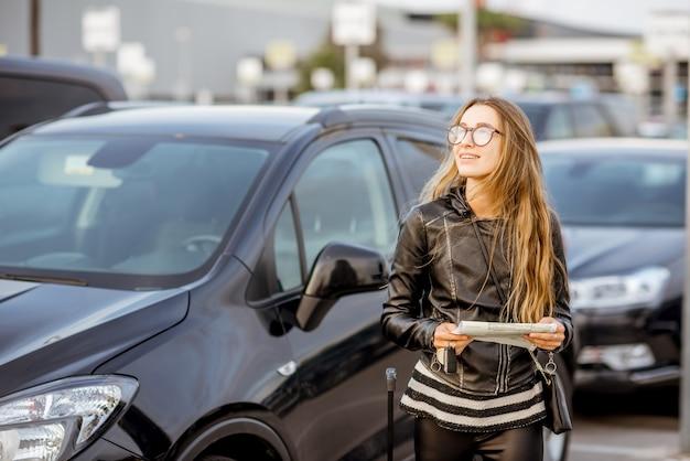 공항 근처 주차장에 야외에서 임대 계약을 하고 서 있는 젊은 여성의 초상화