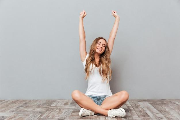 灰色の壁の上の床に座って手を伸ばす若い女性の肖像画