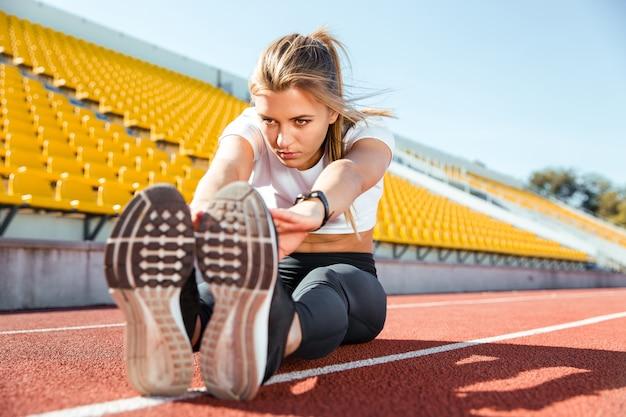 スタジアムの床に伸びる若い女性の肖像画