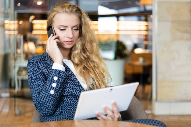 Портрет молодой женщины разговаривает по телефону во время перерыва при использовании цифрового планшета