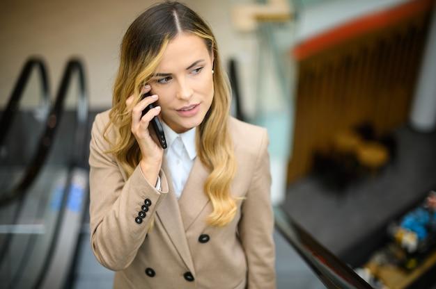 Портрет молодой женщины разговаривает по телефону на мобильной лестнице