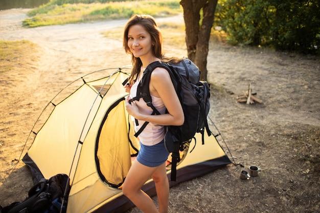 夕暮れ時のテントの近くのバックパックでハイキング若い女性観光客の肖像画