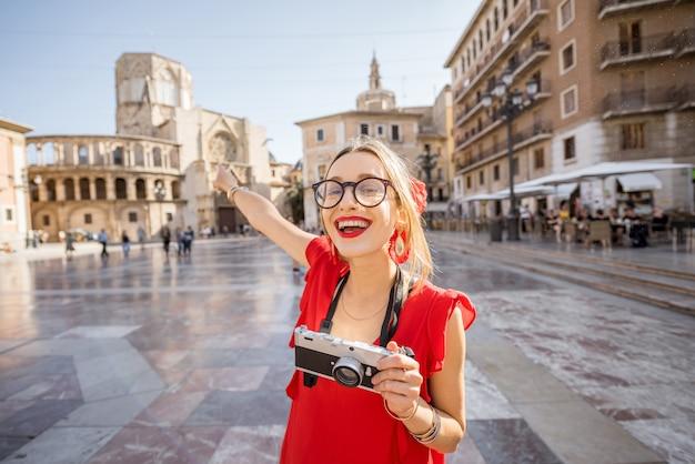 スペイン、バレンシア市の旧市街の中央広場に扇子と赤いドレスを着た若い女性観光客の肖像画