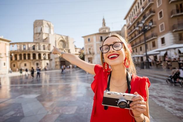 Портрет молодой женщины-туриста в красном платье с веером на центральной площади старого города в валенсии, испания