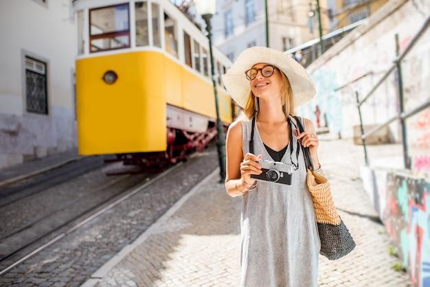 Портрет молодой женщины-туриста, стоящего возле знаменитого желтого трамвая, путешествующего в старом городе лиссабона, португалия