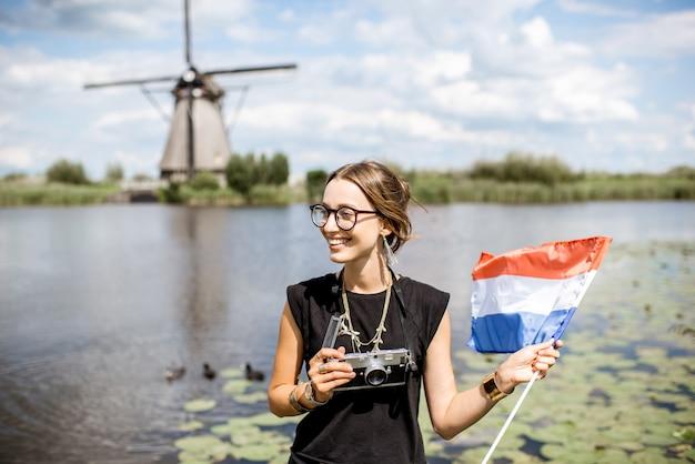 Портрет молодой женщины турист, стоящий с голландским флагом на фоне красивого пейзажа со старыми ветряными мельницами в нидерландах