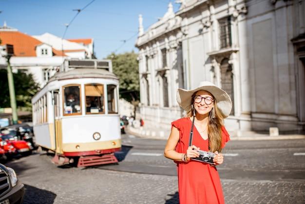 リスボン、ポルトガルの背景に有名な観光トラムと通りに立っている赤いドレスを着た若い女性旅行者の肖像画