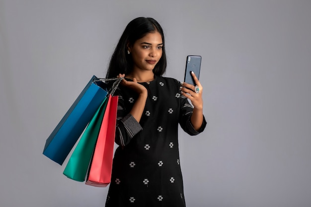 買い物袋を手に携帯電話を使用している若い女性の肖像画。