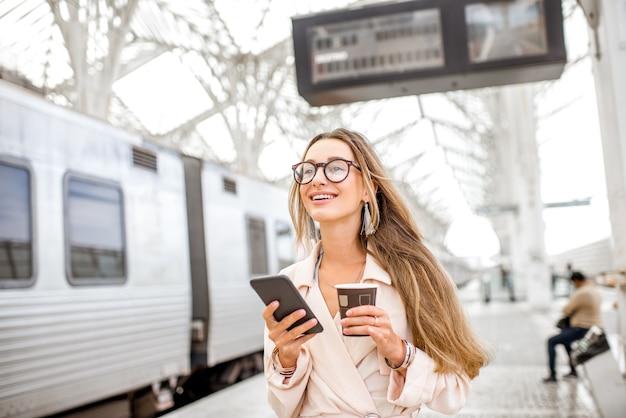 Портрет молодой женщины, использующей смартфон на вокзале с информационным табло на заднем плане