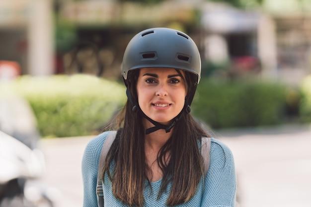 通りでカメラを見ている自転車のヘルメットをかぶっている若い女性の肖像画